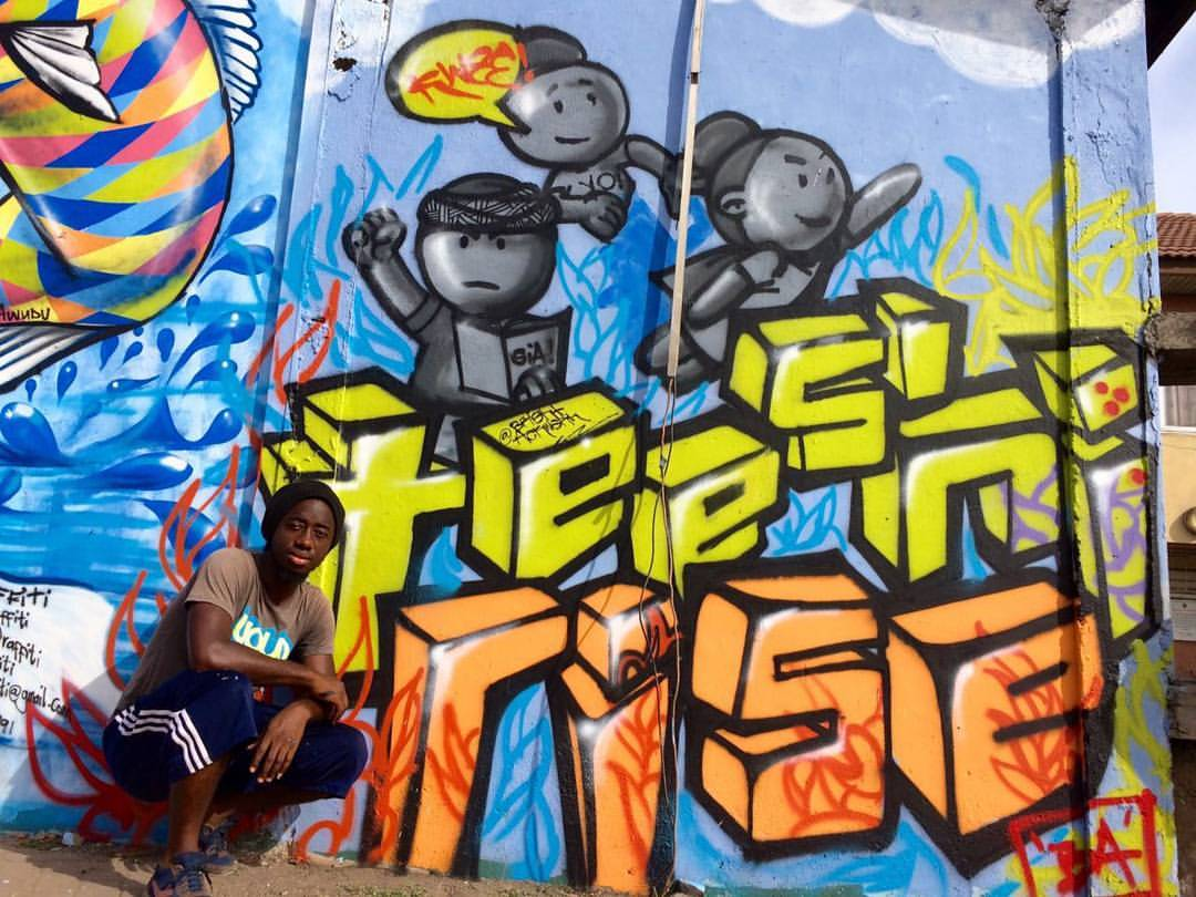 Bright Ackwerh poses beside his mural at the Meetig of Styles Graffitti Experience