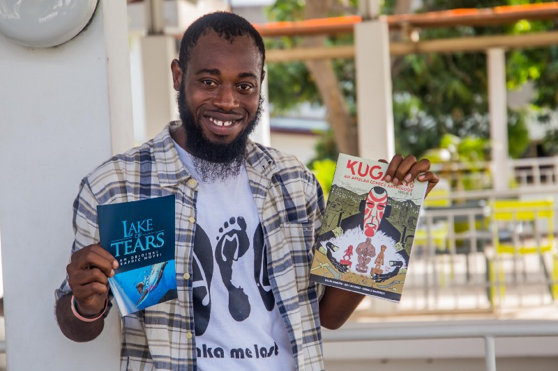 Squid Mag co-founder Kofi Sydney Asare holding up a copy of the Kugali Anthology and a leaflet for the award-winning Lake of Tears graphic novel