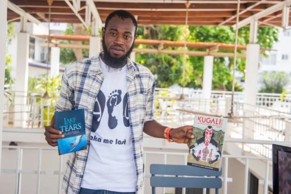 Kofi Sydney Asare holding up the Kugali Anthology and a Lake of Tears brochure at Pa Gya, a Literary Festival In Accra 2017